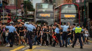Demonstranter korsar en väg i hongkong. Polis visar riktningen.