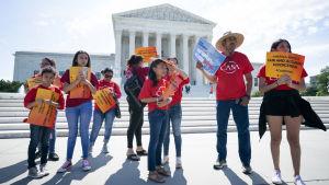En grupp unga demonstranter i röda t-skjortor utanför Högsta Domstolens pampiga marmorbyggnad i Washington.