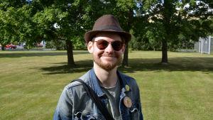 Jerry Lindqvist. Man med hatt och solglasögon i 30-års åldern ler och tittar in i kameran. Grön gräsmatta och gröna träd i bakgrunden.