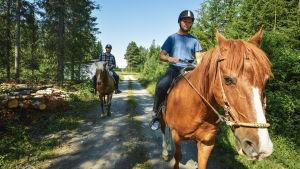 Två män rider på varsin häst längs en skogsväg.