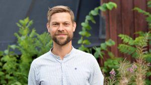 Jon Lindström, turismchef i Hangö, står i en vit murarskjorta framför en röd stugvägg med gröna växter.