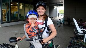 En kvinna står och håller i en cykel där ett barn sitter i en barnstol.