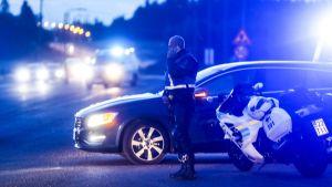 En polis står bredvid en polisbil och en polismotorcykel