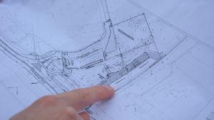 ett pekfinger som pekar på nya hamnområdet på en detaljplan, en karta