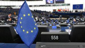 Den blåa EU-flaggan med gula stjärnor i en ring. I bakgrunden kan man se parlamentets mötessal som nästan är tom på folk.