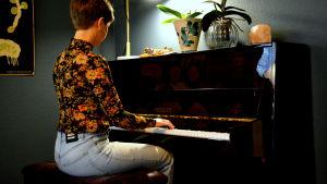 en kvinna i blommig tröja och jeans sitter och spelar piano