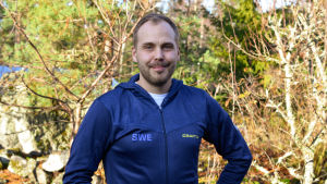 En man med skägg står i solen och ler. Han har en blå jacka med svenska landslagets tryck på.