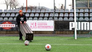 Pele Koljonen bär en bänk på en fotbollsplan.