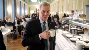 Statsminister Antti Rinne (SDP) med en kaffekopp i handen. Han står i kaféet i riksdagshuset.