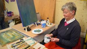 Tetti Sommardahl putsar penslar innan hon målar en tavla.