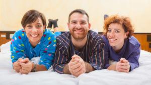 Två kvinnor och en man ligger bredvid varanda på en säng och ler glatt