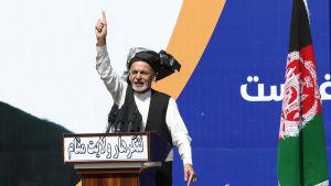 Ashraf Ghani nostaa kättään pystyyn puhuessaan lavalla.