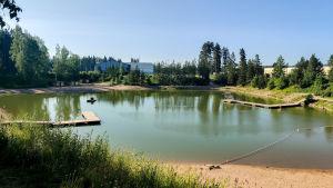 En stor sandgrop fylld med vatten där folk simmar.
