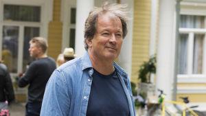 En man i jeansjacka som ler.