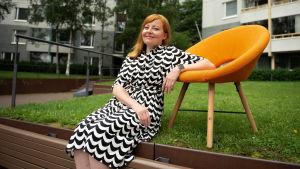 Maria Lindqvist istuu maassa ja nojaa oranssiin tuoliin