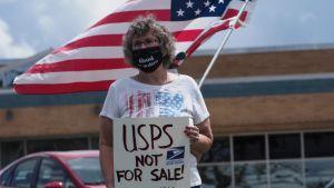 """En kvinna med munskydd håller en skylt i handen med texten """"USPS är inte till salu"""". Bakom henne viftar någon med USA:s flagga."""