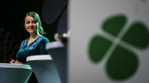 Katri Kulmuni i talarstol med grön fyrklöver på affisch.