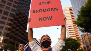 "En demonstrant håller upp ett plakat med texten ""Stop Erdogan now""."