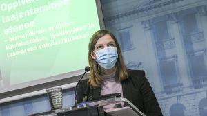 Undervisningsminister Li Andersson står i talarstol och presenterar regeringens förslag om utvidgad läroplikt.