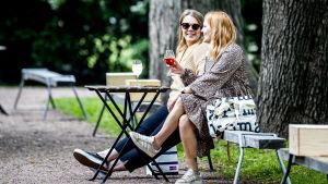 Kaksi naista istuu terassilla puistomaisessa ympäristössä