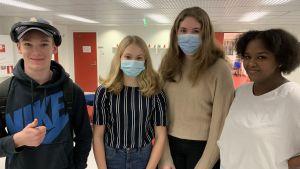 Fyra unga personer står intill varandra i skolmiljö, tittar in i kameran och ler. Två av dem bär munskydd.