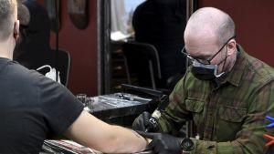 Tony Raita tatuerar en kund.