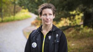Porträttbild av Sanna Hellström på en asfalterad väg i skogen.