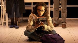 En ung kvinna sitter på golvet och läser en bok. Bakom henne står hennes föräldrar.