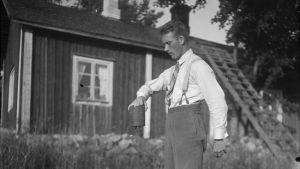 En man lyfter ett tungt lod med sin ena hand. Bilden är tagen 1930 i Bromarf.