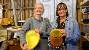 Lena Kolmvik och Patricia Serrander från Stockholm håller i lerkärl med gul insida.