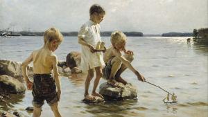 Lekande pojkar på stranden.