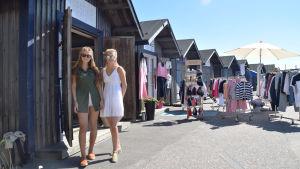 Två unga kvinnor i solglasögon och klänning står bredvid en butik som finns i en stuga. I bakgrunden finns flera likadana blåa stugor och en del kläder som hänger på stänger.