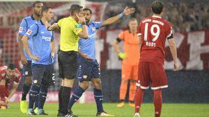 Fotbollsdomare omringas av spelare.
