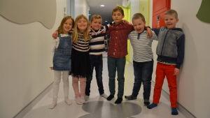 Barn står på rad i en daghemskorridor.
