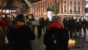 En kvinna talar i megafon och läser upp vittnesmål under me too- demonstration