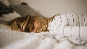 nainen makaa sängyllä ja katsoo kameraan hiuksien takaa