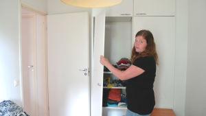 Kvinna håller i skåpdörr som hänger på sned.