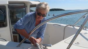 Carina Wolff Brandt förtöjer sin båt vid land.