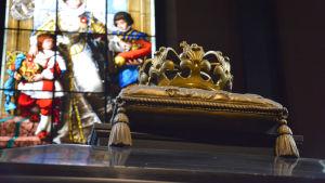 En förgylld krona framför ett målat kyrkglas.
