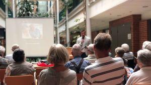 Seniorit istuvat katsomassa esitystä verkkopalveluiden hyödyistä.