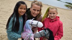Lee och två flickor med käpphästar