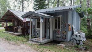Kaksi mökkiä, ruskea ja vaaleansininen, ulkoseiniin kiinnitetty kuvia Elvis Presleystä. Sinisen tuvan kattoon kiinnitetty USA:n ja Suomen liput.