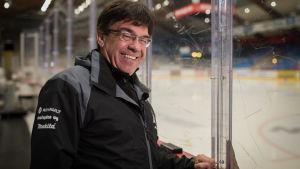 Man står vid ishockeyrink och ler