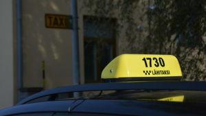 En gul taxiskylt på en taxibil.