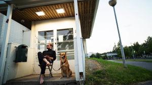 Mies istuu tuolilla lasiovien edessä ja pitää kiinni vieressä istuvan koiran lieasta.