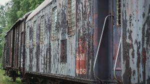 Kulunut, ruosteinen vankien kuljettamiseen tarkoitettu junanvaunu.