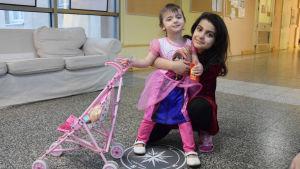 En flicka och hennes syster som leker i rum. Lillasystern drar runt på en vagn med en leksaksdocka.