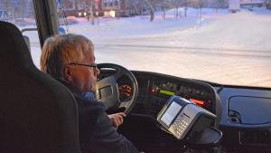En man i medelåldern sitter bakom ratten på en buss. Det är mörkt i bussen, likaså utomhus. Ute synns en snötäckt gata.