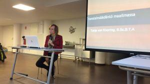 Tanja von Knorring håller en föreläsning med mikrofon i handen och framför en dator.
