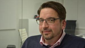 Thomas Grandell, en man med glasögon, kort skägg och mustasch, och en rosa piketskjorta under en blå tröja.